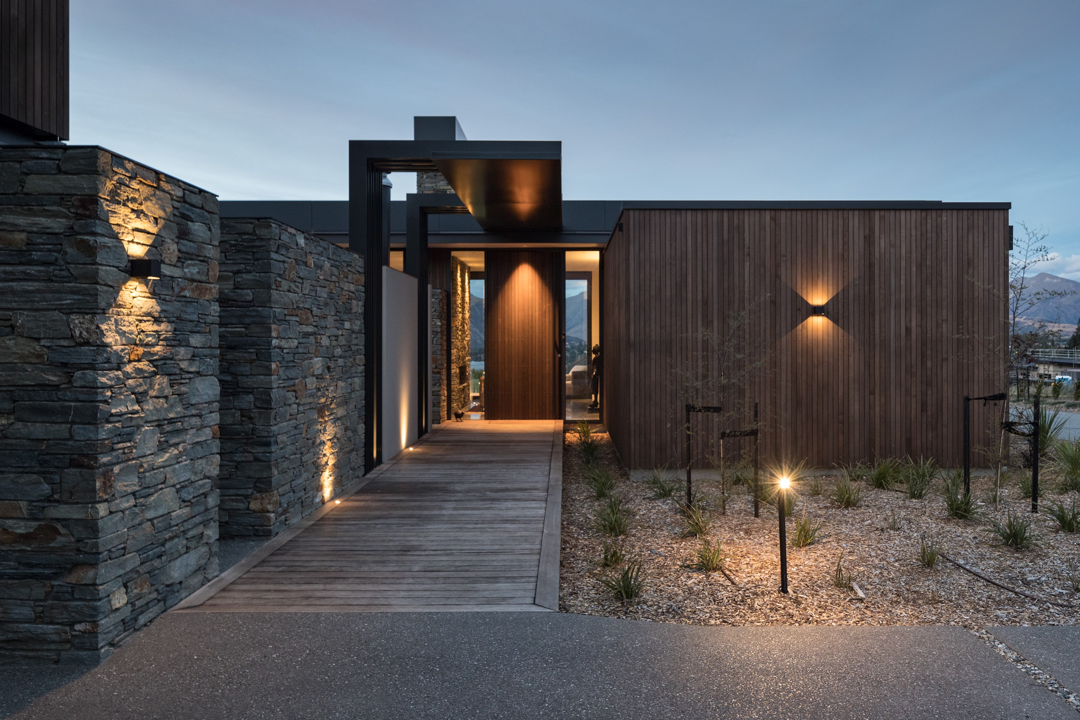 Exterior of modern Wanaka residence mixing stone, wood, and steel